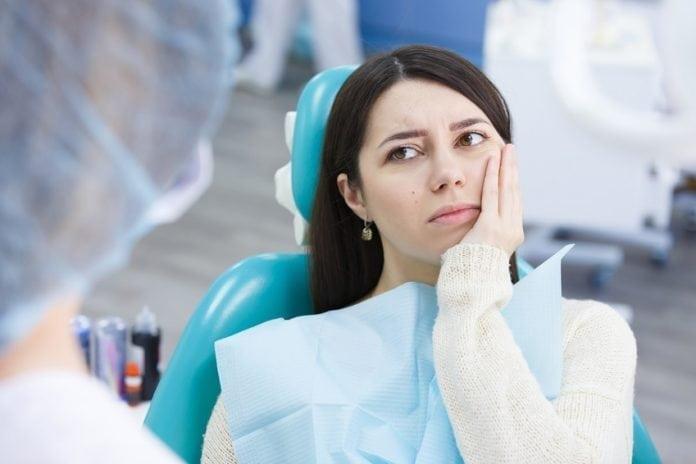 dovod-na-usmev-zubny-kaz-bolest-zuba-zena-u-zubara-s-rukou-na-tvari